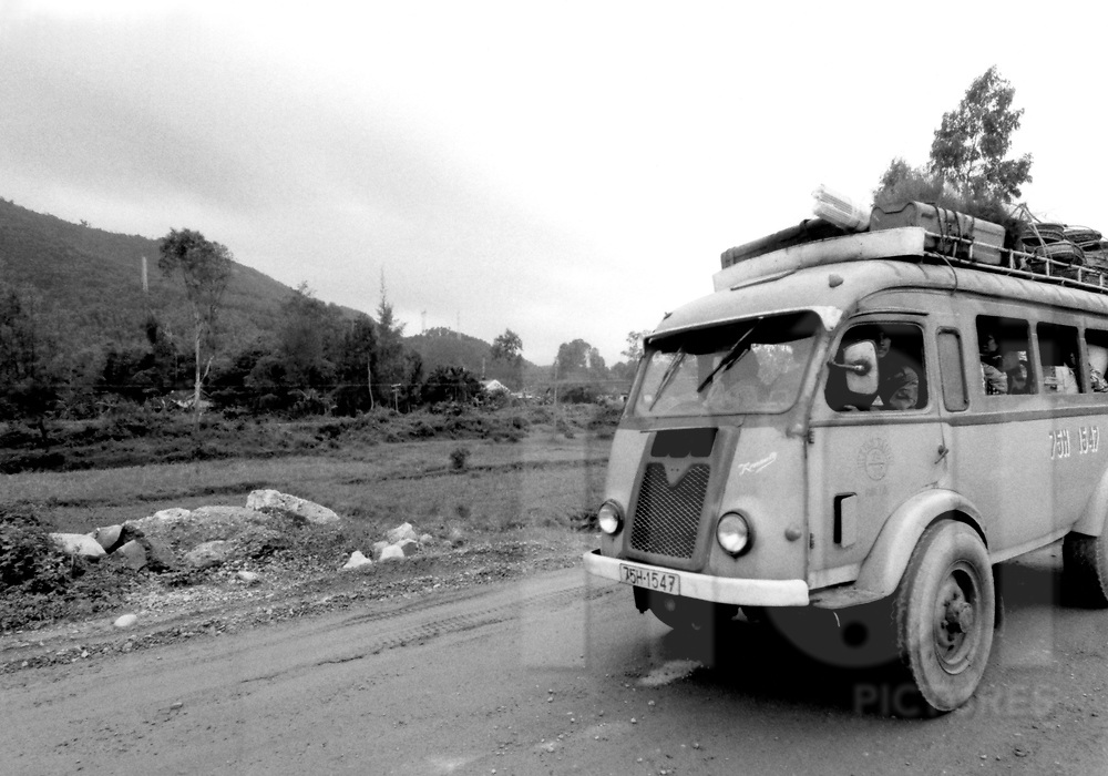 Old french citroën bus rides a track in Hue's countryside, Vietnam, Asia. 1995