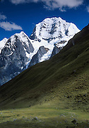 """Trek to see the impressive peak of Siula Grande in the Cordillera Huayhuash, Andes Mountains, Peru, South America. Siula Grande (northeast face, 20,800 feet or 6344 meters elevation) was the subject of the gripping 2003 British docudrama """"Touching the Void."""" In 1985, climbers Joe Simpson and Simon Yates scaled the treacherous Siula Grande, one of the last unconquered mountains in the Andes, but after Joe broke his leg, their descent became one of the most amazing survival stories in mountaineering history. This photo shows the northeast face, but they climbed Siula Grande from a valley on the other side (the west face) and descended along the north ridge, on the upper right. The 2003 movie is based upon Joe Simpson's harrowing book, """"Touching the Void: The True Story of One Man's Miraculous Survival."""""""