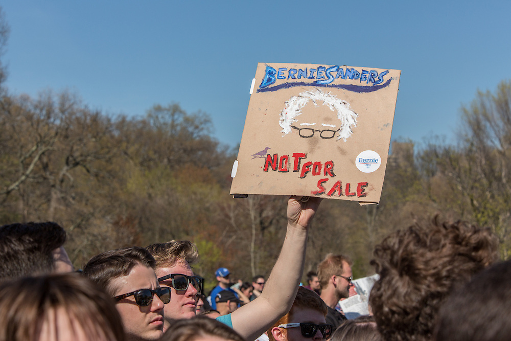 "Brooklyn, NY - 17 April 2016. A man in the crowd holds a dign reading ""Bernie Sanders Not for sale."" Vermont Senator Bernie Sanders, who is running as a Democrat in the U.S. Presidential primary elections, held a campaign ""get out the  vote"" rally in Brooklyn's Prospect Park."