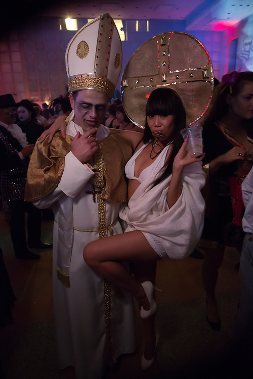 A man costumed as a Pope with a woman costumed as the baby Jesus, with pacifier.