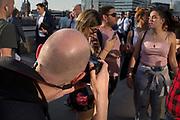 A photographer takes photos of women on London Bridge, on 19th April 2018, in London, England.