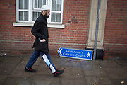 Muslim man walks past a sign for a catholic church which has fallen to the ground, on a wet rainy day in Whitechapel, East End of London, UK.