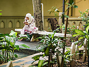 06 JULY 2016 - BANGKOK, THAILAND:  A woman uses her smart phone in the cemetery at Ton Son Mosque in the Thonburi section of Bangkok before Eid services at the mosque. Eid al-Fitr is also called Feast of Breaking the Fast, the Sugar Feast, Bayram (Bajram), the Sweet Festival or Hari Raya Puasa and the Lesser Eid. It is an important Muslim religious holiday that marks the end of Ramadan, the Islamic holy month of fasting. Muslims are not allowed to fast on Eid. The holiday celebrates the conclusion of the 29 or 30 days of dawn-to-sunset fasting Muslims do during the month of Ramadan. Islam is the second largest religion in Thailand. Government sources say about 5% of Thais are Muslim, many in the Muslim community say the number is closer to 10%.       PHOTO BY JACK KURTZ