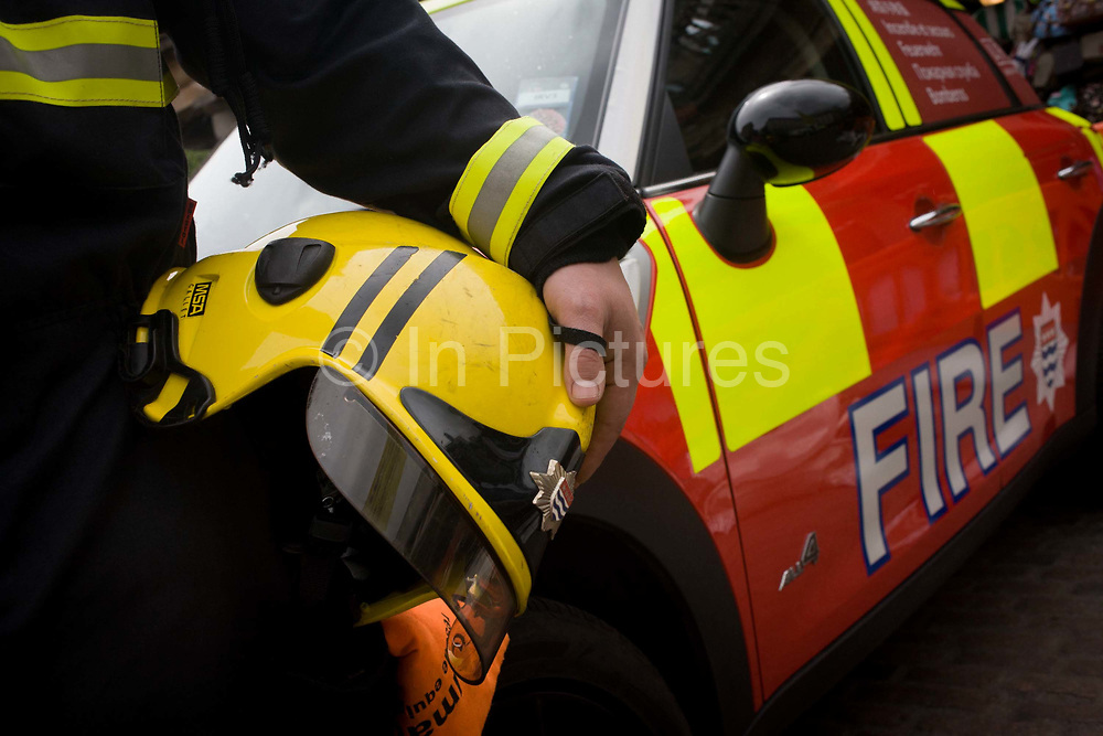 Detail of a firefighter's helmet and a London Fire Brigade's Mini car after the LFB's 'extrication' team with the Vehicle and Operator Services Agency (VOSA) gave a demonstration on how firefighters rescue passengers by cutting open with dedicated cutting equipment a stretch limousine in London's Covent Garden Piazza. Highlighting the dangers of hiring illegal luxury or novelty cars, this vehicle was seized last year with many mechanical defects rendering it unsafe for those inside with limited exit doors. Of 358 cars stopped in March 2012, 27 were seized and 232 given prohibitions.