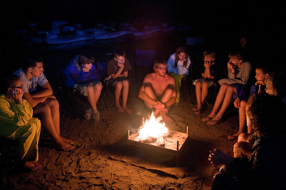 North America, United States, Colorado, Dinosaur National Monument, Green River (Gates of Lodore section), people in circle around campfire.  MR