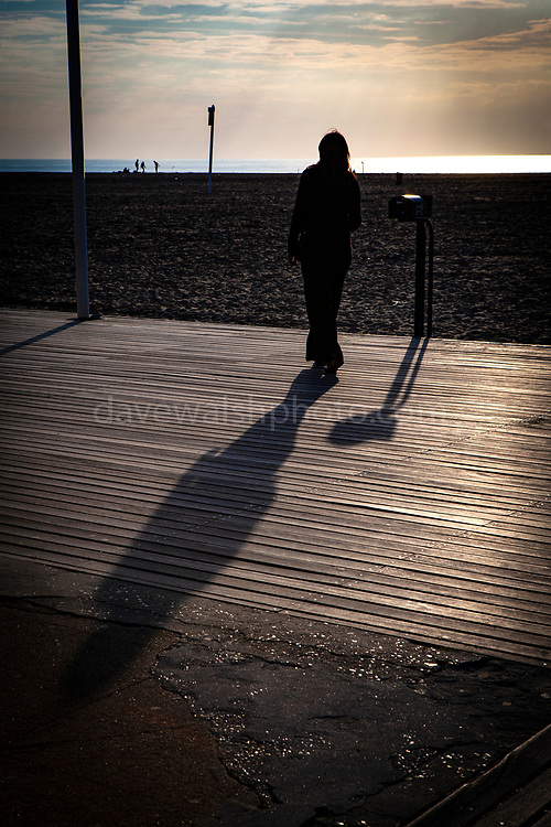 Woman on the boardwalk at sunset, Les Planches, Deauville, Normandy, France