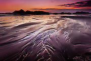 The receeding tide leaves patterns etched in the sand at sunset on the Oregon Coast