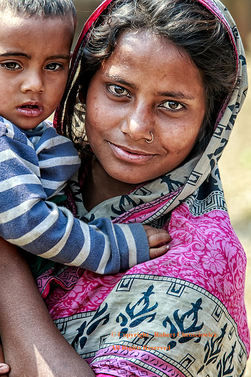 Mother & Child: A kind woman in traditional dress holds her child, Dhaka Bangladesh.