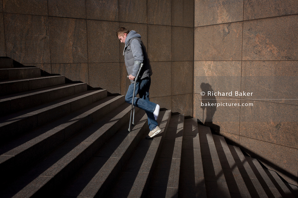 Young man hobbles up steep steps, hopping on one foot with the aide of crutches.