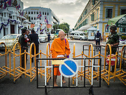 07 JULY 2015 - BANGKOK, THAILAND:  A Buddhist monk walks through a military checkpoint in front of the Ministry of Defense in Bangkok before a rally to support students arrested by the military. About 100 people gathered in front of the Ministry of Defense in Bangkok Tuesday to support 14 university students arrested two weeks ago for violating orders against political assembly. They're facing criminal trial in military courts. The courts ordered their release Tuesday because they can only be held for two weeks without trial, the two weeks expired Tuesday and the military court chose not to renew their pretrial detention. The court order was not an acquittal. They still face trial and possible prison sentences if convicted.       PHOTO BY JACK KURTZ