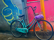 Blue Bicycle parked against a graffiti painted wall with a thumbs up sign.