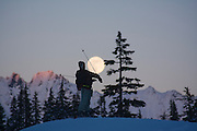 A lone skier, silhouetted against the moon, raises his ski poles in celebration and awe on a tour in the Mount Baker backcountry, Washington.