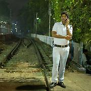 A policeman on duty along a train track.