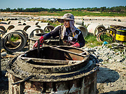 """13 FEBRUARY 2019 - SIHANOUKVILLE, CAMBODIA: A Cambodian worker makes cement sewage lines that will be used in Sihanoukville to improve infrastructure for the Chinese hotels and casinos being built there. There are about 80 Chinese casinos and resort hotels open in Sihanoukville and dozens more under construction. The casinos are changing the city, once a sleepy port on Southeast Asia's """"backpacker trail"""" into a booming city. The change is coming with a cost though. Many Cambodian residents of Sihanoukville  have lost their homes to make way for the casinos and the jobs are going to Chinese workers, brought in to build casinos and work in the casinos.      PHOTO BY JACK KURTZ"""