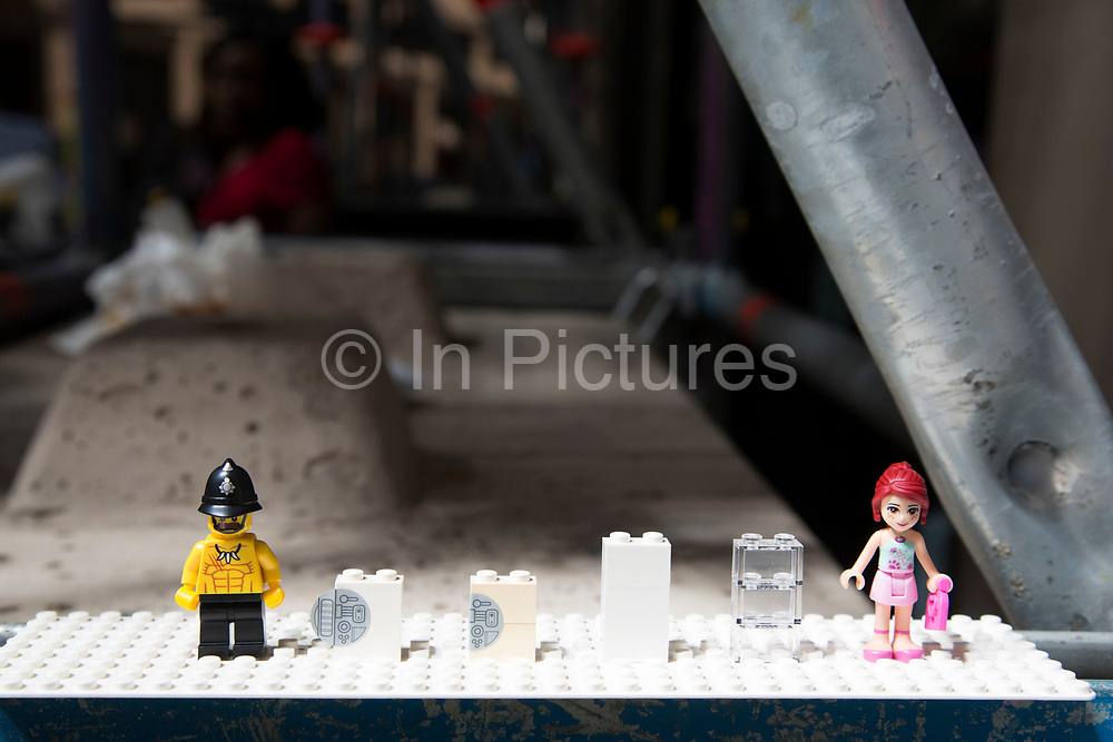 """London, UK. Wednesday 4th September 2013. Lego figures set up to see if they melt. Urgent action in planned to """"cover up"""" the Walkie Talkie skyscraper in the City after sunlight reflected from the building melted a car on the streets below. Temperatures have been measured in excess of 50 degrees C, and as much as 70 degrees at it's peak. The 525ft building has been renamed the """"Walkie Scorchie"""" after its distinctive concave surfaces reflected a dazzling beam of light which has caused extensive damage to nearby buildings."""