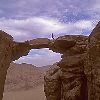A hiker stands atop a huge rock arch on Jebel [Mount] Burdah, in the Wadi Rum, Jordan.