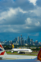 Jets taxiing on the runway at Sydney Airport (with the Sydney skyline behind), Sydney, New South Wales, Australia