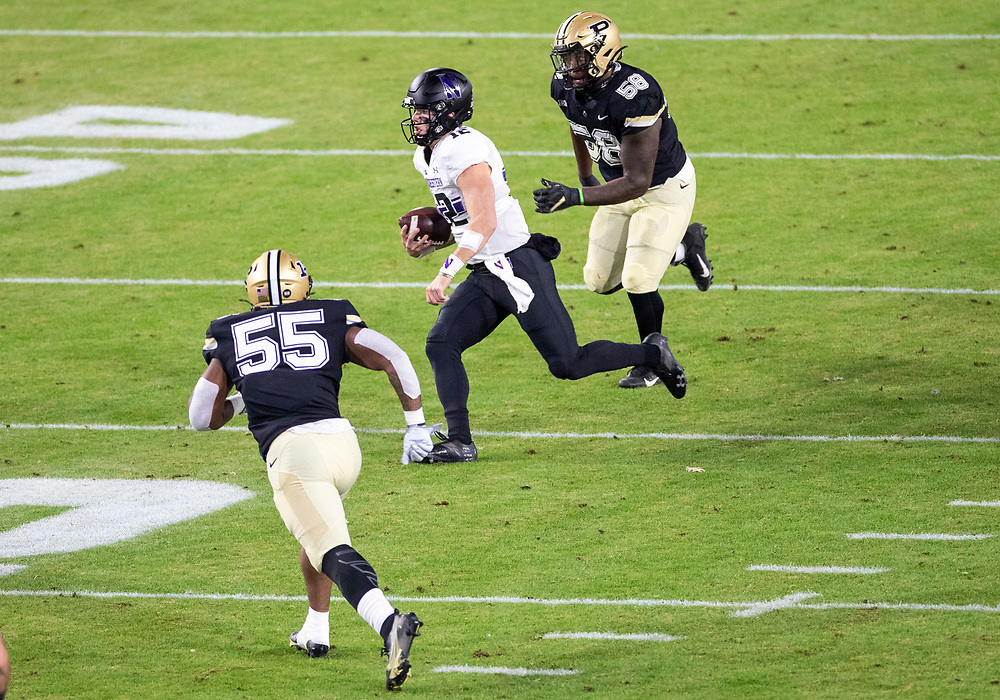 November 14, 2020:  Northwestern quarterback Peyton Ramsey (12) runs with the ball as Purdue defenders pursue  during NCAA football game action between the Northwestern Wildcats and the Purdue Boilermakers at Ross-Ade Stadium in West Lafayette, Indiana. Northwestern defeated Purdue 27-20.  John Mersits/CSM.