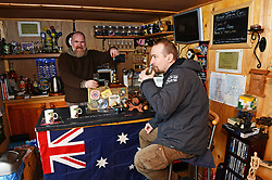 EXCLUSIVE: An Australian man has created his own Outback outpost 11,000 miles from home on the Shetland Islands – and he even has WALLABIES. Tasmanian Dave Kok, 42, has built his own Aussie oasis on the Scottish archipelago after deciding to settle there when he was travelling Europe. Now Dave lives with his Shetland native wife Louise, 38, and two daughters Caitlin, 11, and Ruby, aged four. Social care worker Dave came to the islands in the late 90s and since 2016 has been building his own watering hole choc-full of Australiana on the island of Burra. Dave's place 'The Outpost' is a renovated wooden porta cabin filled with Tasmanian beers, Tim Tams, books on bush craft and Aussie Rules sporting memorabilia. Locals use the Outpost as their local bar and meeting place, as the nearest pub or café is three bridges and three islands away. And visitors can now enjoy the Outpost's wallabies Ned and Kelly who David brought to the island this winter. Based on the Shetland Islands latitude the marsupials could be the most northerly of their species anywhere on the planet. Dave said visiting Australians are often surprised to find the antipodean paradise in such a remote location. 16 Feb 2018 Pictured: Pic from Dave Donaldson/ Magnus News Agency. Pic shows David Kok with a happy local at the bar of his Aussie-themed Outpost in the Shetland Islands. An Australian man has created his own Outback outpost 11,000 miles from home on the Shetland Islands – and he even has WALLABIES. Tasmanian David Kok, 42, has built his own Aussie oasis on the Scottish archipelago after deciding to settle there when he was travelling Europe. Now David lives with his Shetland native wife Louise and two daughters Caitlin, 11, and Ruby, aged four. Social care worker David came to the islands in the late 90s and has built his own watering hole choc-full of Australiana on the island of Burra. David's place 'The Outpost' is a renovated wooden porta cabin filled with Tasmanian beers, Ti