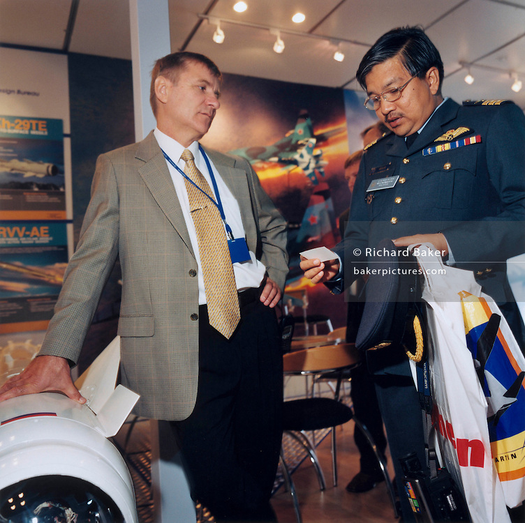 A Russian Mikoyan employee stands alongside a Malaysian air force officer examining the seller's business card during the bi-annual aerospace industry expo at the Farnborough airshow in southern England. We see the seller as a man in brown jacket with hand on hip, looking unimpressed and bored while the officer in full dress uniform peering at the card intently, carrying his shopping bag containing information from other manufacturers around the aviation fair. Farnborough is organised by Farnborough International Limited, a wholly owned subsidiary of ADS Group Limited (ADS). According to the organisers, the 2012 Farnborough show attracted 109,000 trade visitors over the first five days, and 100,000 public visitors on the Saturday and Sunday. Orders and commitments for 758 aircraft were announced, worth US$72 billion.