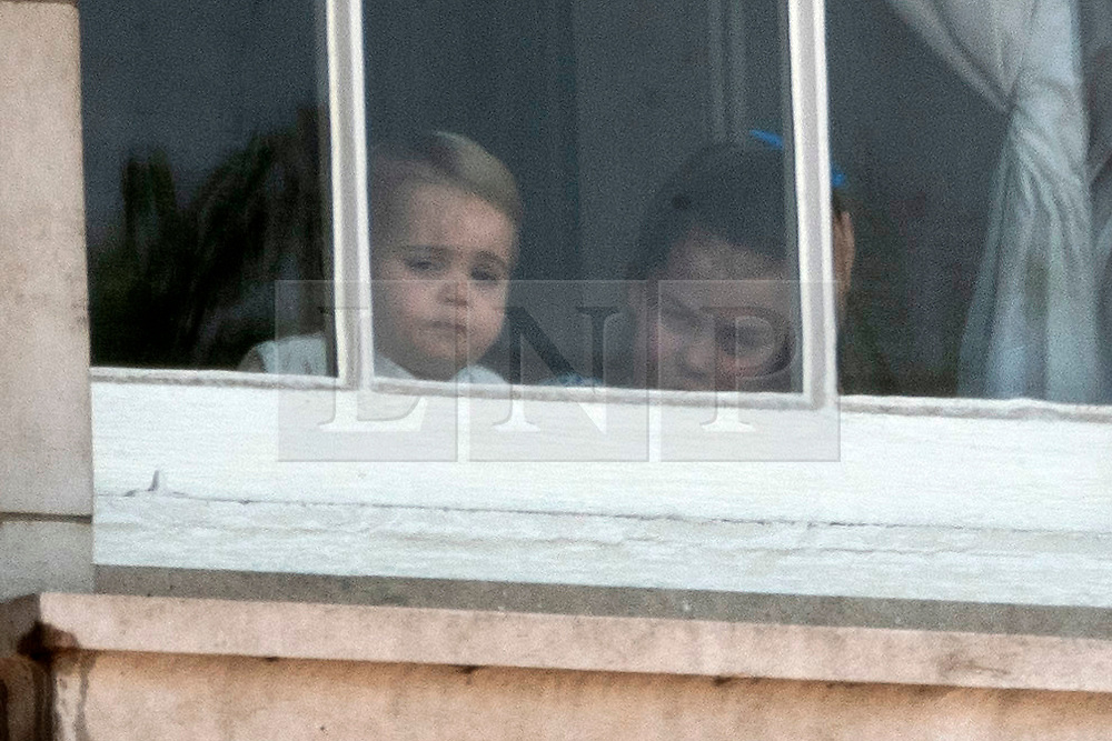© Licensed to London News Pictures. 08/06/2019. London, UK. Prince Louis and Princess Charlotte look through a Buckingham Palace window during the Trooping the Colour ceremony to mark Queen Elizabeth II's 93rd birthday. Photo credit: Ray Tang/LNP