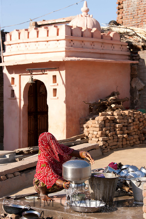 Indian woman washing pots at home in Narlai village in Rajasthan, Northern India