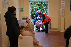 © Licensed to London News Pictures. 15/01/2021. London, UK. A patient arrives at a vaccination centre in White City, west London. Staff work round the clock administering vaccines at a target rate of one every minute, expecting to exceed a daily total of over 500 jabs.The centre has been set up with the associated cold chain in place to distribute thePfizer-BioNTech COVID-19 vaccine, servicing patients from high risk groups. Photo credit: Guilhem Baker/LNP