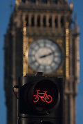 A red cycling light in the foreground and the clockface containing the Big Ben bell in the Elizabeth Tower of the British parliament, on 17th January 2017, in London England.