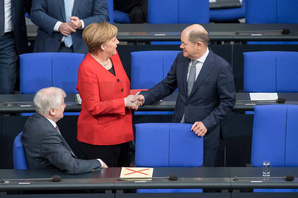21 MAR 2019, BERLIN/GERMANY:<br /> Horst Seehofer (L), CSU, Bundesinnenminister, Angela Merkel (M), CDU, budneskanzlerin, und Olaf Scholz (R), SPD, Bundesfinanzminister, im Gespraech, vor Beginn der Bundestagsdebatte zur Regierungserklaerung der Bundeskanzlerin zum Europaeischen Rat, Plenum, Deutscher Bundestag<br /> IMAGE: 20190321-01-011<br /> KEYWORDS: Gespräch, Handshake