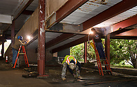 Dan Smith and Jeremy Young weld the ramp girders while Justin Begalle measures to cut steel plates during repair work to Laconia's downtown parking garage on Friday afternoon.  (Karen Bobotas/for the Laconia Daily Sun)