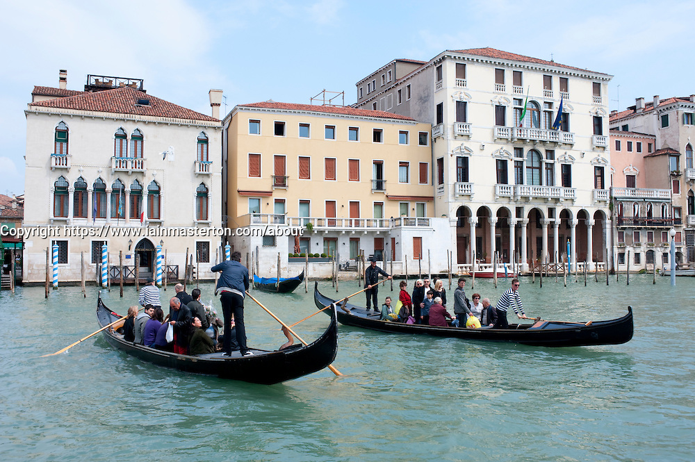 Two traditional traghetto public ferry gondolas ferrying people across Grand Canal in Venice Italy