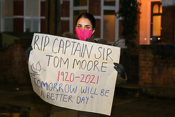 © Licensed to London News Pictures. 03/02/2021. London, UK. A woman takes part in the 'National clap for Captain Sir Tom Moore' in Haringey, North London, by holding a sign that says 'RIP Captain Sir Tom Moore 1920-2021. Tomorrow Will Be A Better Day'. The 100-year-old veteran died on Tuesday, 2 February. Captain Tom raised almost £33 million for the National Health Service (NHS) by walking 100 laps in his garden, before his 100th birthday.  Photo credit: Dinendra Haria/LNP