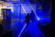 Couple walks through blue laserlight at MIAT, industrial museum of ghent, belgium, 03.12.2015