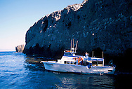 Island Packers ferry boat floating in coastal cove below sheer rock cliff, Anacapa Island, Channel Islands National Park, California