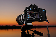 a sunset on the monitor of a camera taken with another digital camera in a riverside during real time sunset