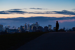 """A walker is seen against the backdrop of the city's pre-dawn skyline on Primrose Hill. The threatened snow from """"The Beast From The East"""" weather system doesn't materialise overnight in London leaving a crisp, clear morning, seen from Primrose Hill in North London. London, February 27 2018."""