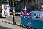 On the day that the EU in Brussels agreed in principle to extend Brexit until 31st January 2020 aka Flextension and not 31st October 2019, a tour bus drives past Brexit Party flags and banners during a Brexit protest outside parliament, on 28th October 2019, in Westminster, London, England.