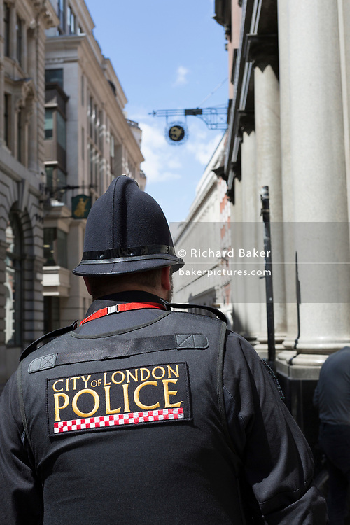 Beneath the signs and architecture of banking and financial institutions, a City Police officer walks down Lombard Street in the City of London, the capital's financial district, on 17th June 2019, in London, England.