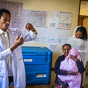 INDIVIDUAL(S) PHOTOGRAPHED: From left to right: Nega Alemneh, Embet Matebe, Mariamawit Mikiyas (child), and Birtukan Mekonen. LOCATION: Mecha Health Center, Bahir Dar, Ethiopia. CAPTION: Mariamawit Mikiya is held by her relative while nurse Nega Alemneh prepares an injection for the baby. The baby's mother observes from behind.