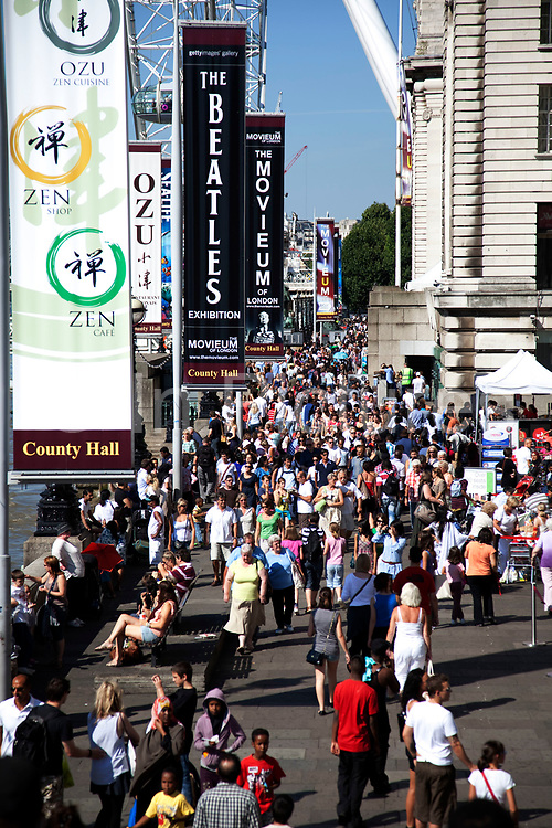 Crowds of tourists gather along the Southbank of the River Thames near to the London Eye. This are is one of the busiest places for tourism. With thousands passing through each day. Art galleries and other attractions are also the main draw.