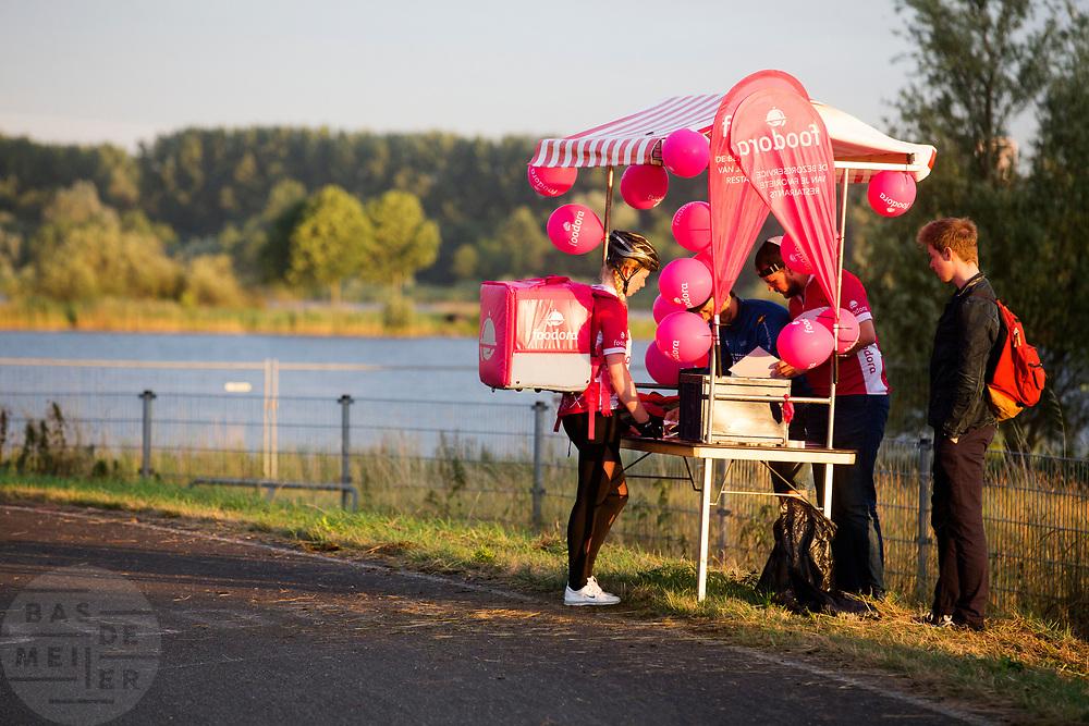 Een bezorger van Foodora haalt haar opdracht op bij een checkpoint van het bedrijf. In Nieuwegein wordt het NK Fietskoerieren gehouden. Fietskoeriers uit Nederland strijden om de titel door op een parcours het snelst zoveel mogelijk stempels te halen en lading weg te brengen. Daarbij moeten ze een slimme route kiezen.<br /> <br /> A messenger of Foodora gets her assignment at a checkpint of Foodora. In Nieuwegein bike messengers battle for the Open Dutch Bicycle Messenger Championship.
