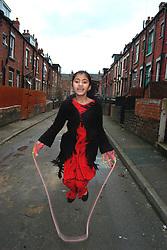 Girl skipping; playing on the street Beeston Leeds UK