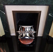 Art Deco fire place with silver plated fire grate.