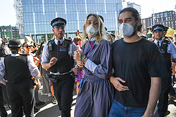 © Licensed to London News Pictures. 31/05/2020. London, UK. A woman is arrested and led off by police. Demonstrators gather in front of the US Embassy in London, protesting the police killing of George Floyd, an unarmed black man in Minneapolis who died in police custody while an officer kneeled on his neck to pin him down. Photo credit: Guilhem Baker/LNP