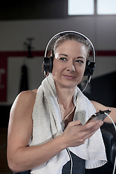 Young woman listening to music in the gym during the break, Bavaria, Germany