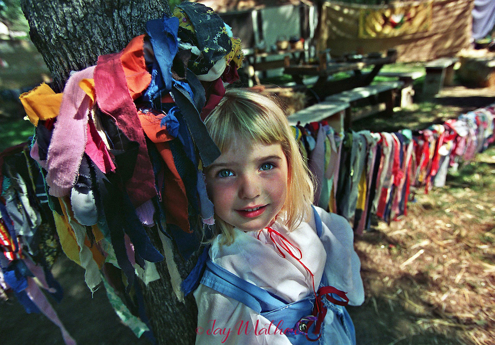"""Rachael Covington, 3, framed by a rag rope around an oak tree pauses during the Fair Oaks """"Renaissance Tudor Fayre.""""   The 13th annual fair sponsored by the Fair Oaks Park and Recreation district,  attracted about 800 particiapants in Renaissance costumes singing, dancing and eating their way through the two-day event."""