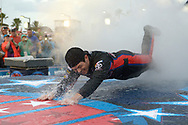 Ryan Truex dives on the rain-slick runway during driver introductions before the NASCAR Sprint Cup Series auto race at the Daytona International Speedway in Daytona Beach, Fla., Saturday, July 5, 2014. The race was later postponed until Sunday morning.(AP Photo/Phelan M. Ebenhack)