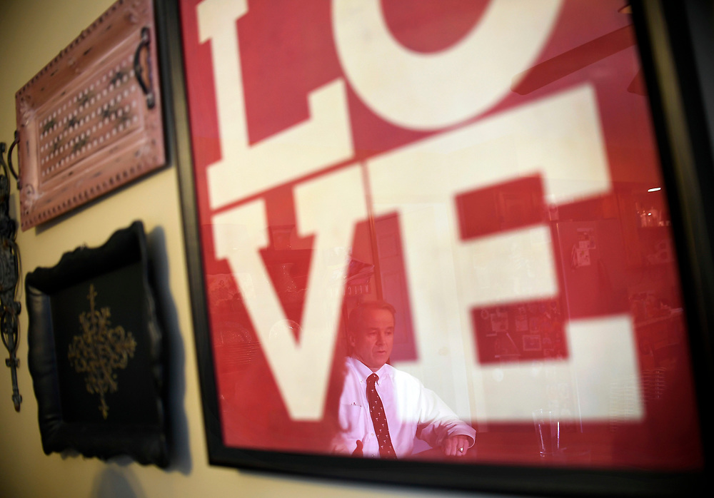Dr. William Begg is reflected in a LOVE print at his home, Thursday, Nov. 9, 2017 in Newtown, Conn. Begg, a Newtown resident, and head of the emergency room and EMS services at Danbury Hospital. He was in charge of patient care on the day of the Sandy Hook shootings in 2012. (Jessica Hill for the New York Times)