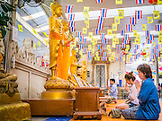 """12 OCTOBER 2012 - RAI KHRING, NAKHON PATHOM, THAILAND:  Thai Buddhists pray at Buddha statues in Wat Rai Khring in Nakhon Pathom province. Wat Rai Khring was built in 1791. The Abbot at the time, Somdej Phra Phuttha Chan (Pook), named the temple after the district. When construction was completed, the Buddha image was brought from another temple and enshrined here. Later locals named the image """"Luang Pho Wat Rai Khing"""". The Buddha image is of Chiang Saen style and is assumed to have been built by Lanna Thai and Lan Chang craftsmen.     PHOTO BY JACK KURTZ"""