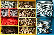 Colourful carpentry box of metal screws viewed rom above